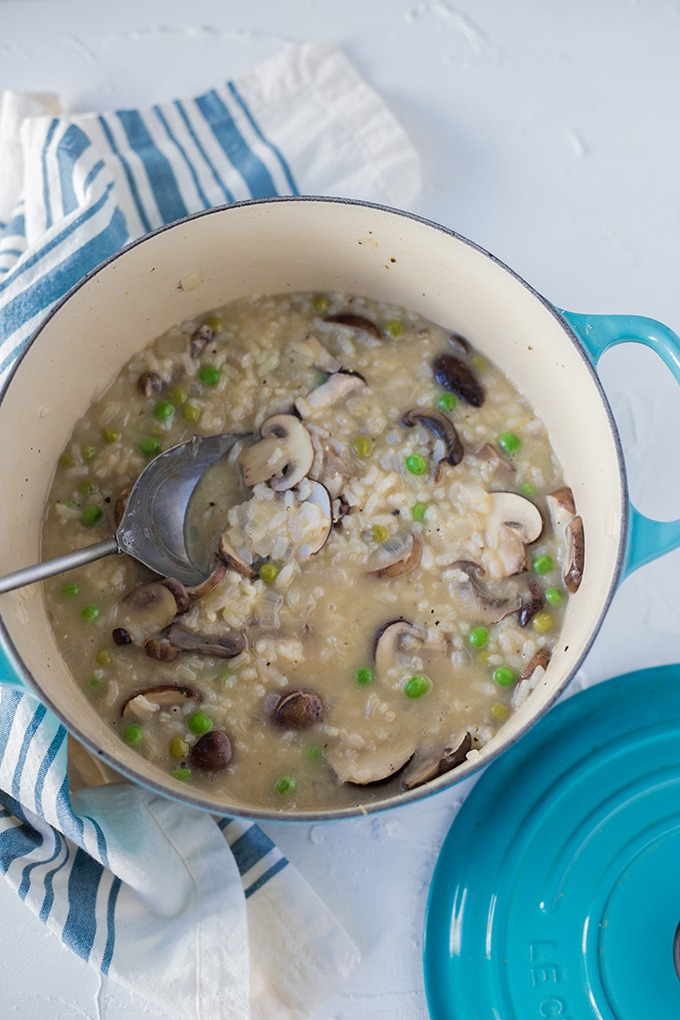 mushroom and pea risotto in a blue dutch oven on a blue and white linen