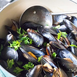 blue dutch oven with rosé mussles, antique scoop and garnished with parsley