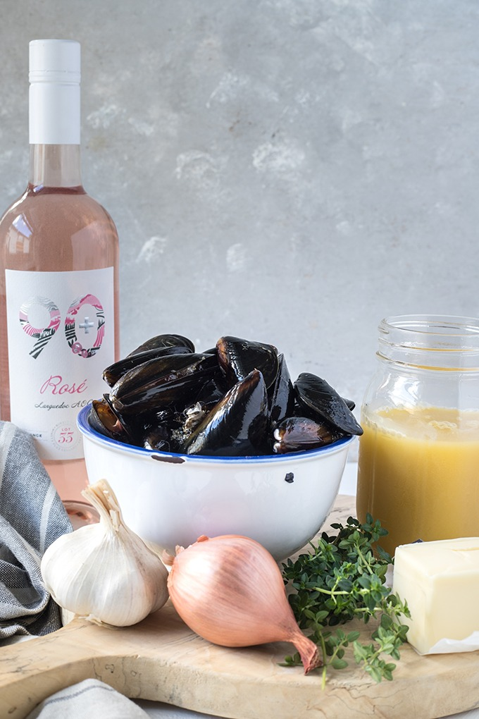rosé wine mussels recipe ingredients on wooden board, left to right. rosé wine, mussels, chicken broth in jar, stick of butter, fresh thyme, one shallot and garlic clove