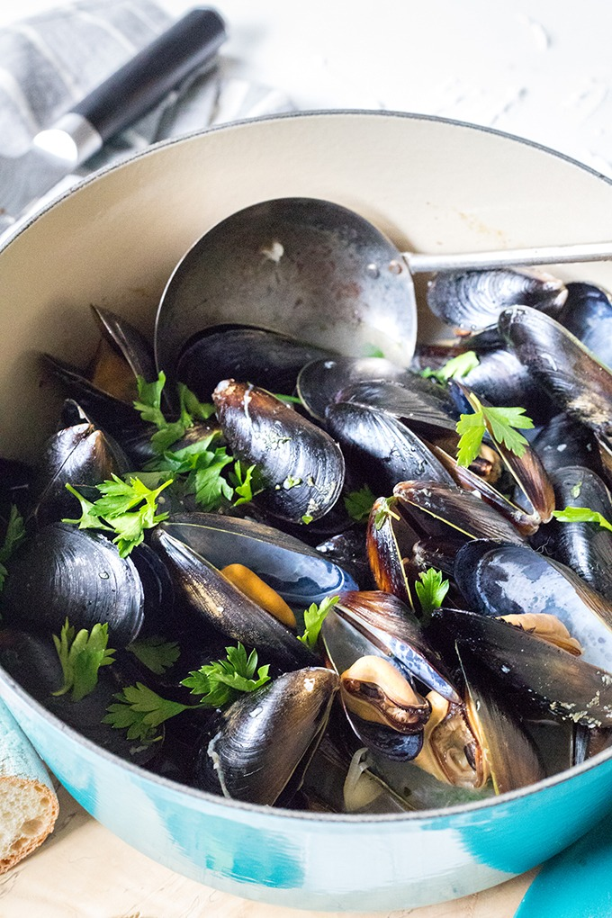 blue dutch oven filled with rosé wine mussels with antique spoon