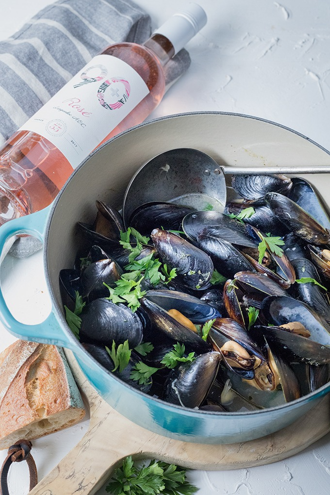 dutch oven pot of wine mussels on wooden antique board front of 90+ cellars bottle of rosé wine