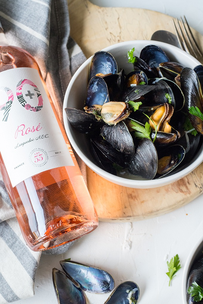 white bowl of wine mussels on wooden board right of a bottle of 90+ cellars rosé wine