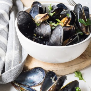 bowl of rosé mussels on an antique board next to a grey linen