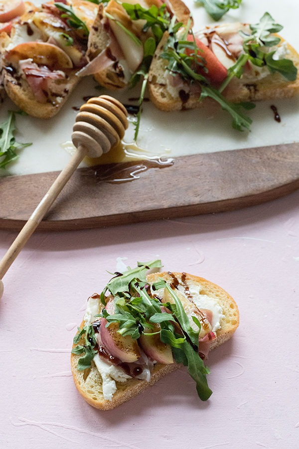 one piece of bruschetta with proscuitto nectarine and arugula on pink board in front of marble board
