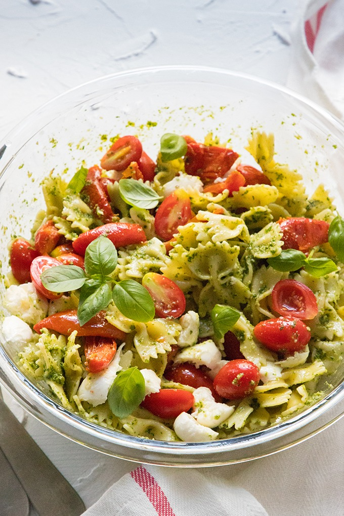 pesto caprese pasta salad in large glass salad bowl
