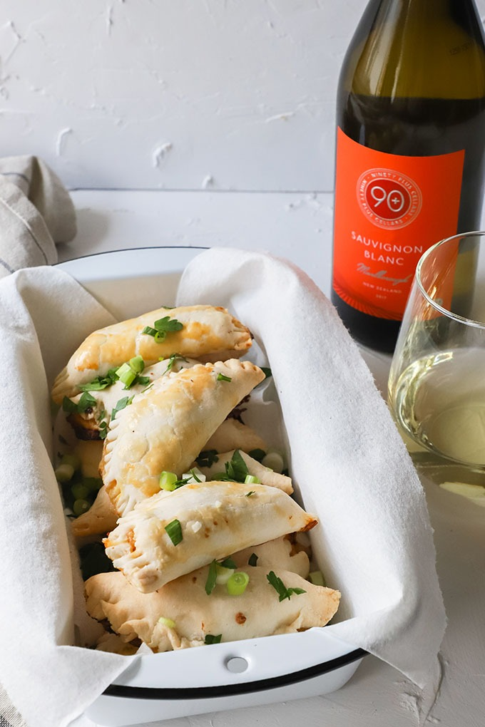 shrimp empanadas in an enamel loaf pan next to bottle and glass of white wine