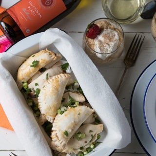 empanadas in an enamel loaf tin, below bottle of white wine and dulce de leche mousse pots
