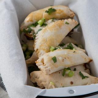 shrimp empanadas in a black and white enamel loaf pan, on a grey napkin