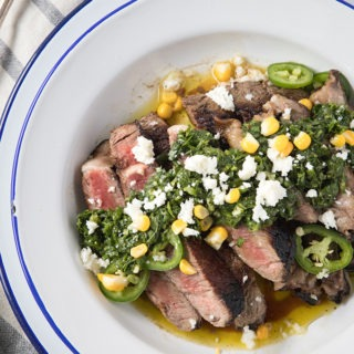 steak with chimichurri sauce on a blue and white enamel plate