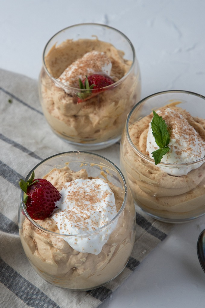 three glasses of dulce de leche mousse on grey napkin