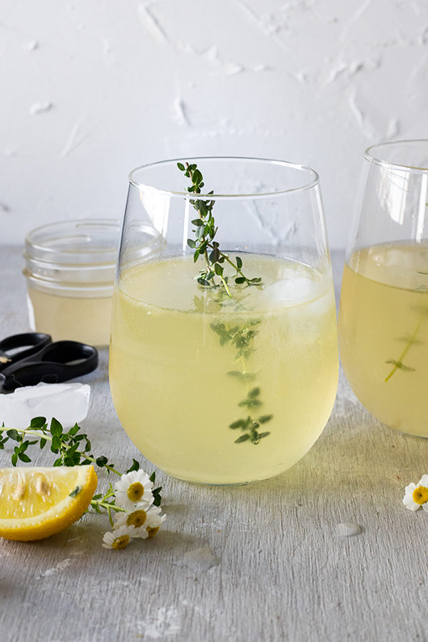 white wine spritzer on grey board, lemon wedges and chamomile flowers around glass