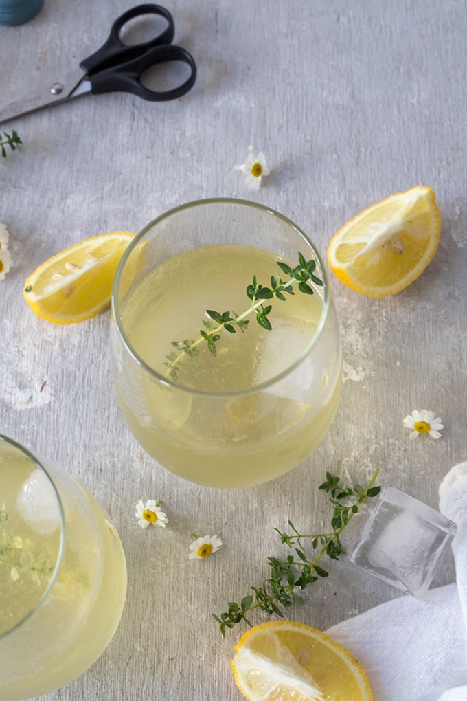 overhead of white wine spritzers in wine glass, surrounded by lemon wedges, thyme leaves, chamomile flowers and small black scissors