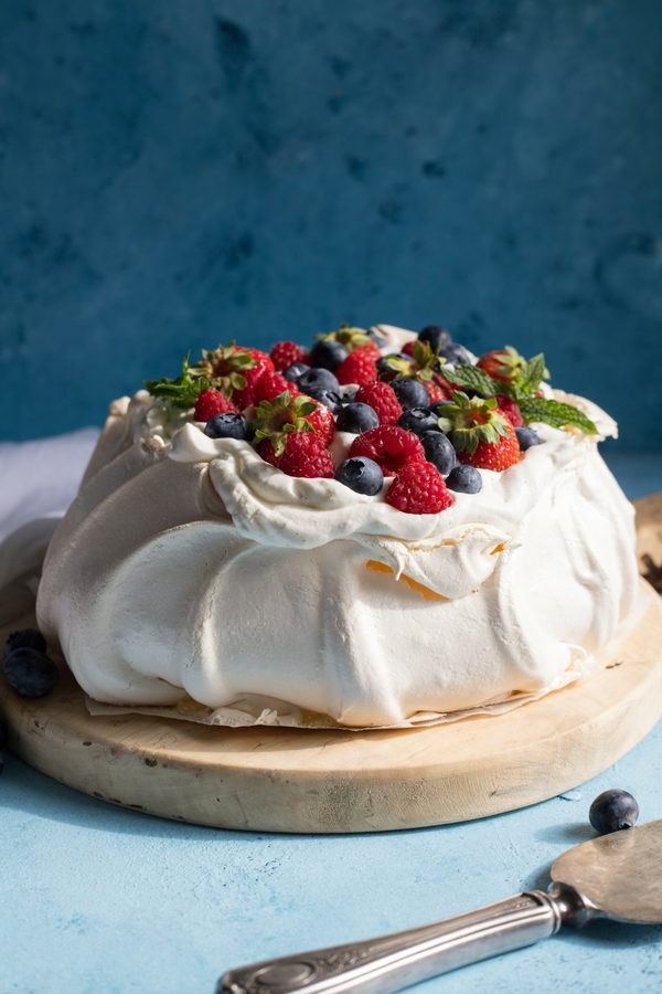 pavlova topped with cream and berries on an antique round wooden board