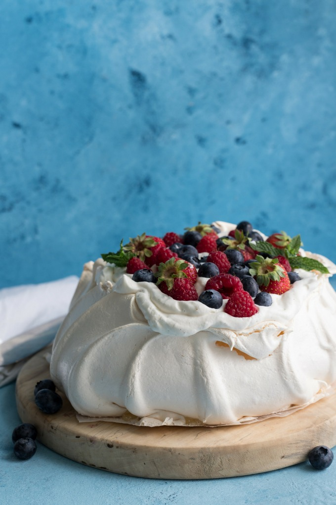 pavlova on antique wooden board covered in fresh cream and berries