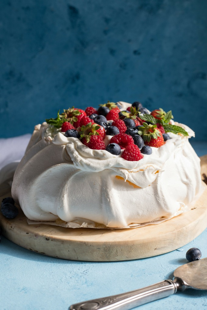 pavlova topped with fresh berries and cream on a wooden round antique board on blue background