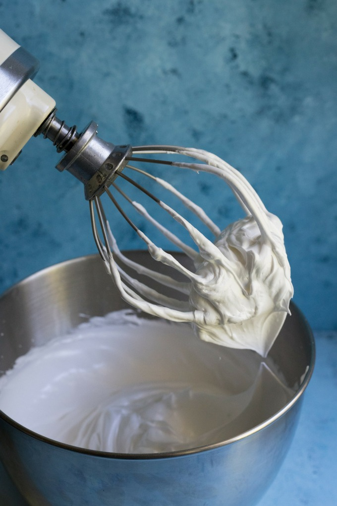 thick and glossy meringue mixture on a whisk attached to a kitchen aid