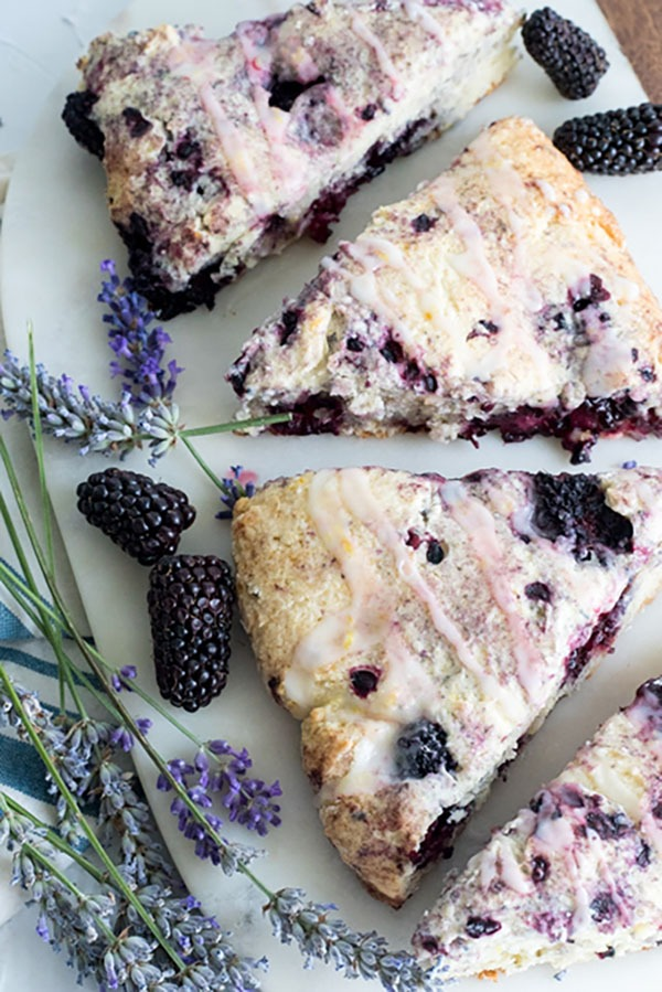 three blackberry scones on a marble board with fresh lavender and blackberries