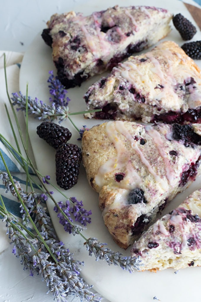 close up of blackberry scones on a marble board with fresh lavender and blackberries