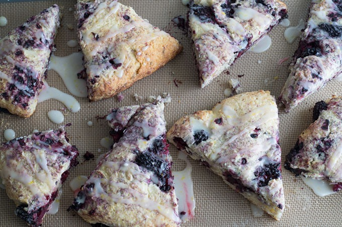 blackberry scones on silicone baking mat, drizzled with lemon glaze