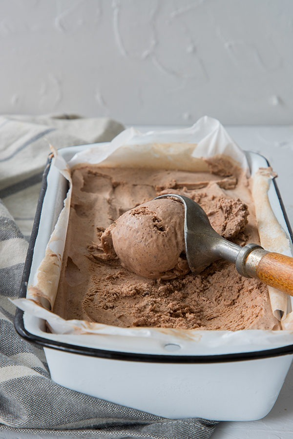 old wooden ice cream scoop, laying on chili chocolate ice cream in white enamel tin