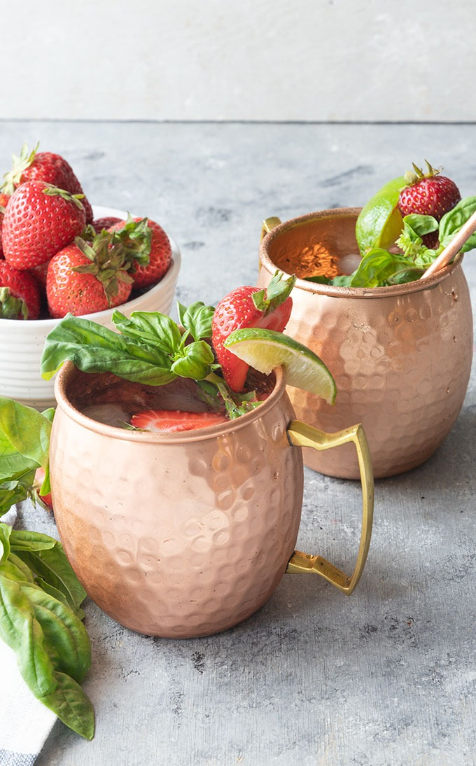 two strawberry basil mule mugs on grey board