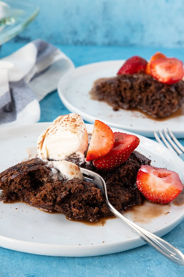 chocolate self saucing pudding on white plate with fork and strawberries