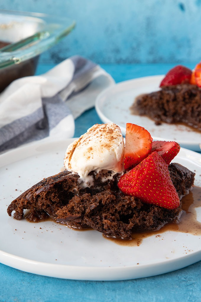 chocolate self saucing pudding on white plate with ice cream and strawberries