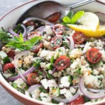 israeli couscous salad in white terra-cotta bowl with antique spoon