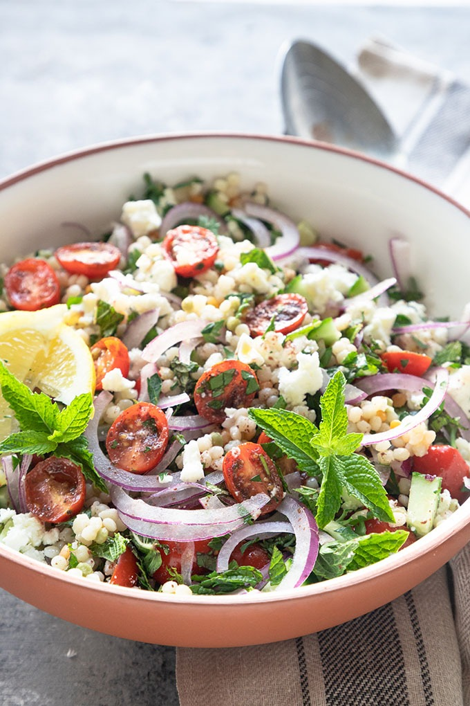 israeli couscous salad in white terracotta bowl