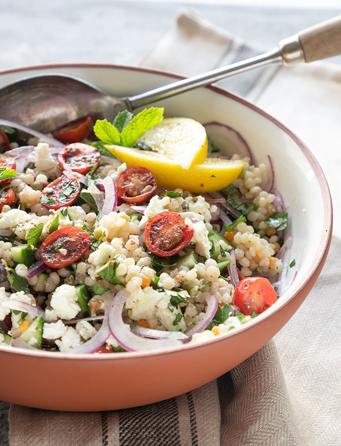 israeli couscous salad in white terra-cotta bowl