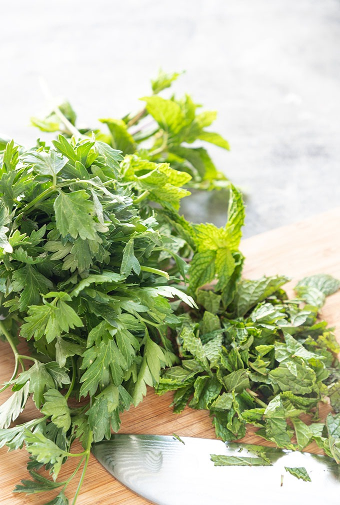 fresh mint and parsley on wooden cutting board