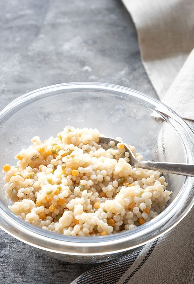 cooked israeli couscous in clear bowl