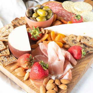 meat and cheese board featured with glass of red wine