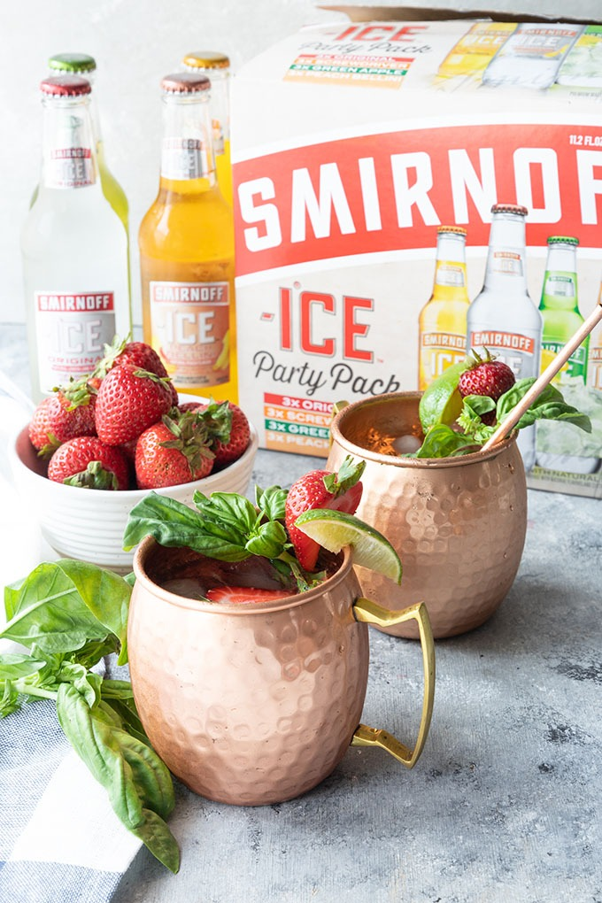 two strawberry basil mule mugs in front of Smirnoff ice party pack, and four bottles of Smirnoff ice