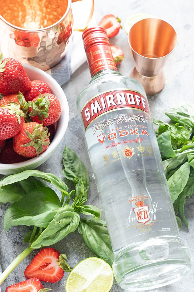 Smirnoff vodka bottle laying flat surrounded by strawberries, basil and copper measuring cup