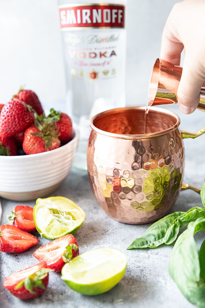 hand pouring a shot of vodka into a Moscow mule mug