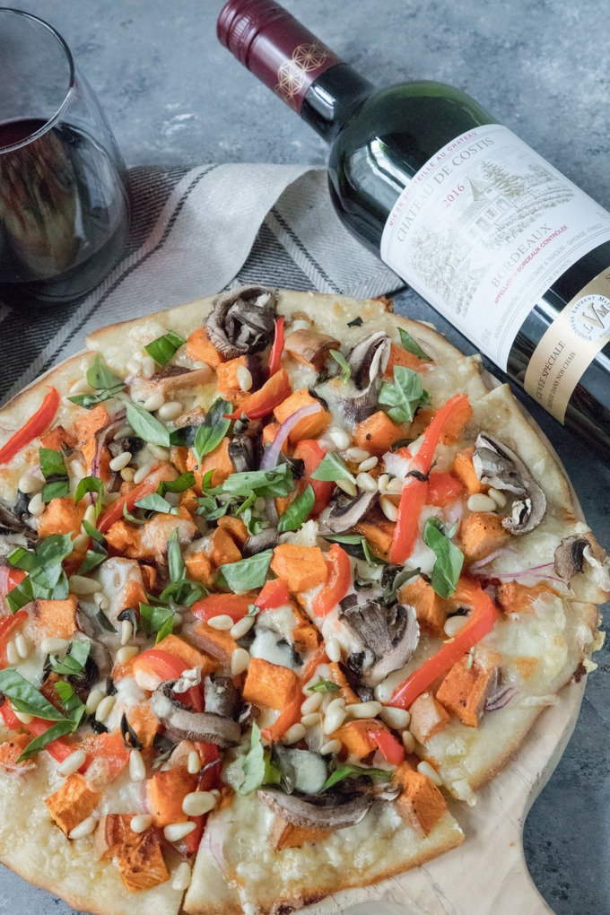 veggie pizza on wooden board with bottle of wine