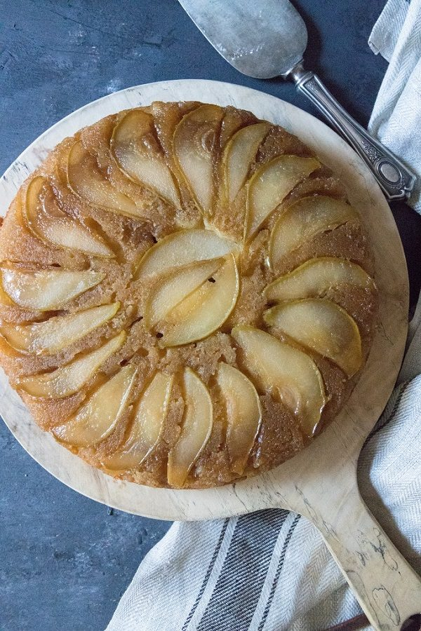 pear upside-down cake on a round wooden board