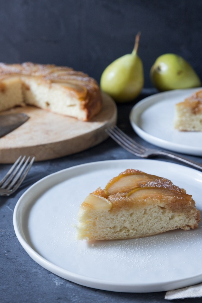 slice of pear upside-down cake on white plate with cake in background