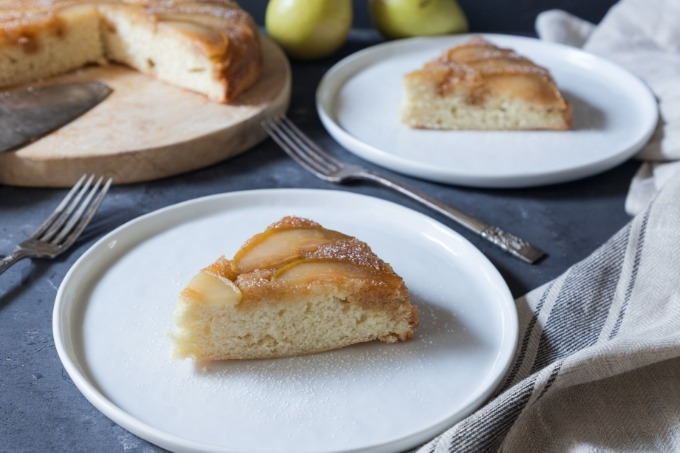 two slices of pear upside-down cake on white plates