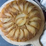 pear upside-down cake on antique round wooden board