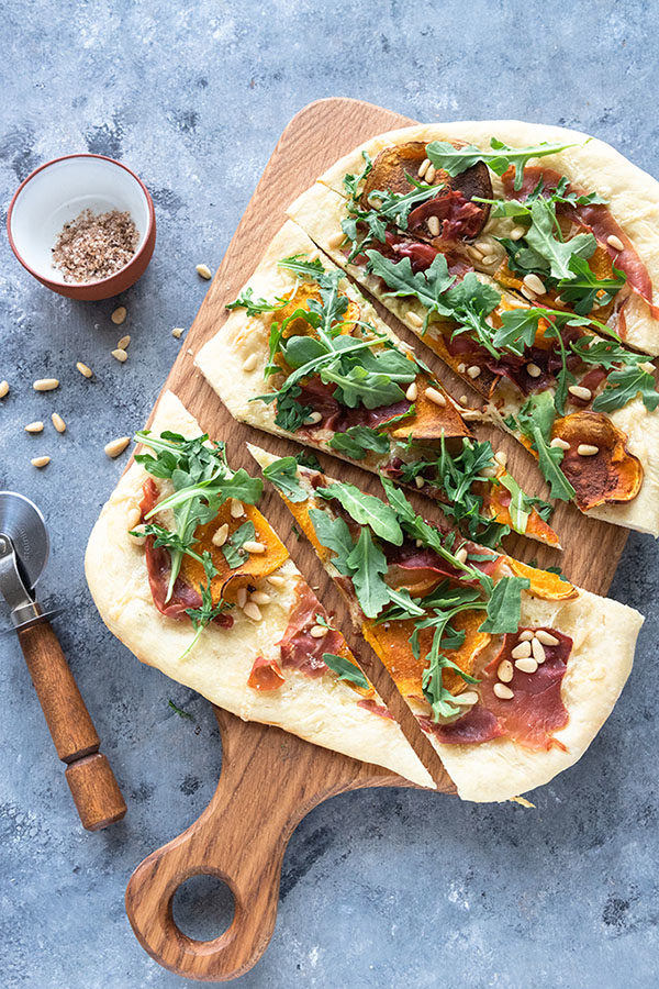butternut squash pizza on a wooden board next to pizza cutter and salt dish