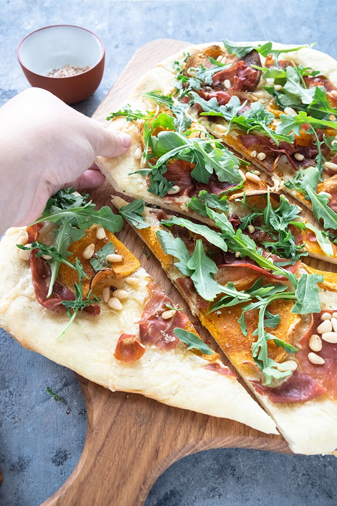 hand reaching out to grab a slice of butternut squash pizza