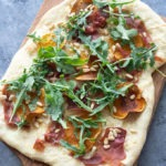 uncut butternut squash pizza on wooden board