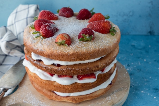 fluffy sponge cake with strawberries on wooden board