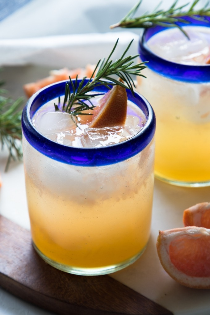 grapefruit gin cocktail in clear glass with blue rim garnished with rosemary and grapefruit