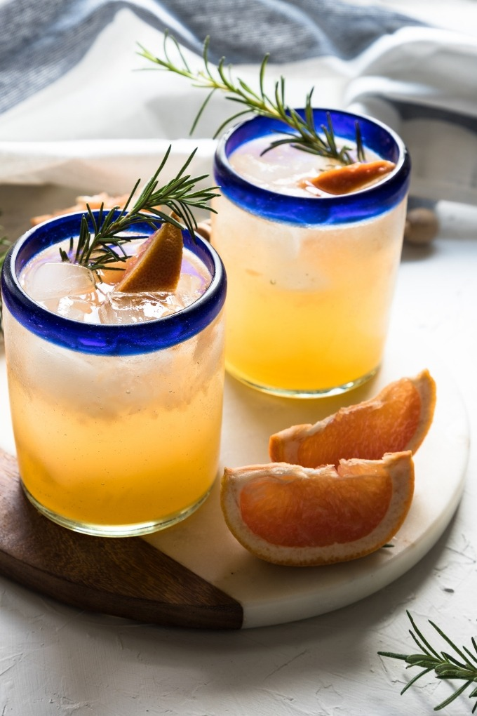 two grapefruit gin cocktail glasses on white marble board