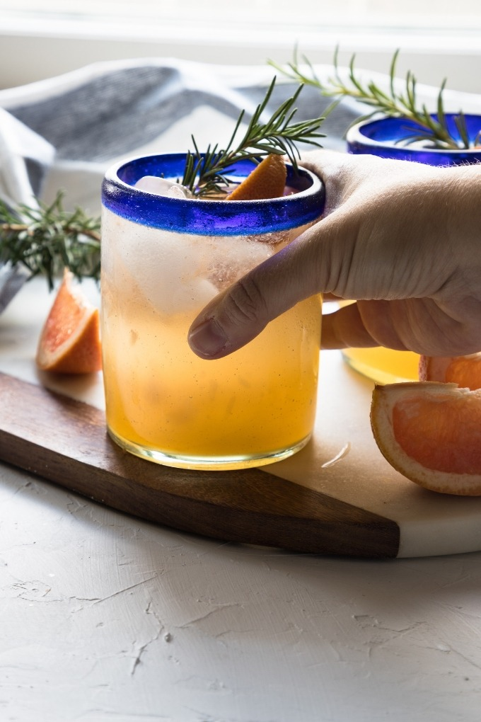 hand reaching out to grab a grapefruit gin cocktail