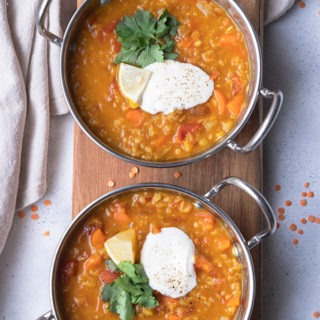 two pots of red lentil dal on wooden board