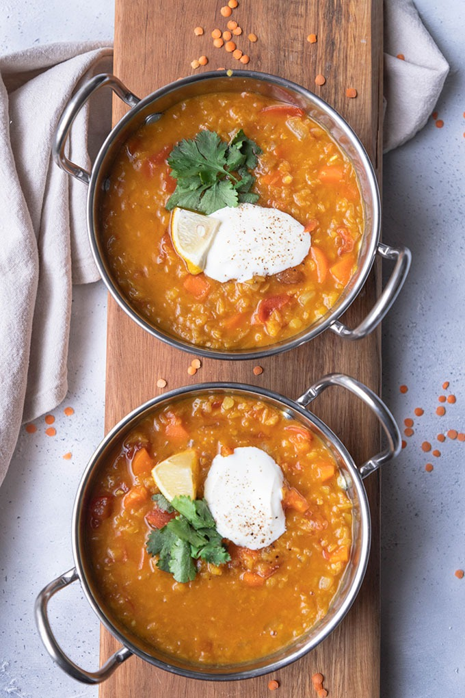 two pots of lentil dal on wooden board